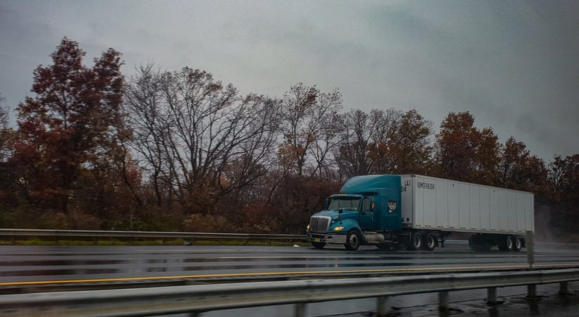 Large blue truck driving down
